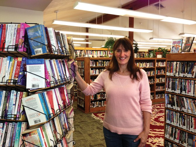 Hayden Public Library Director Ana Lash stands next to the freebie rack. The West Routt Library District has a population of about 2,500 and circulates 3,200 materials monthly.