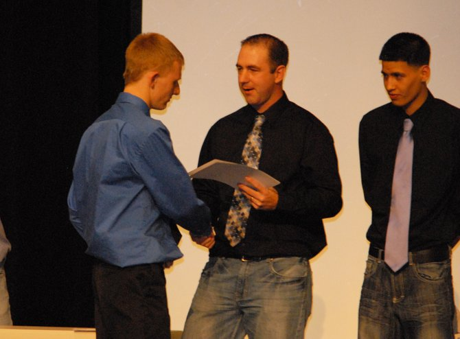 Tyler Davis, left, a Moffat County High School sophomore, accepts his varsity letter at the banquet for the boys and girls basketball teams Tuesday. Davis was Moffat County's leading scorer on the season, and recognized as a first-team All-Western Slope League performer as well as an All-State honorable mention selection by The Denver Post.