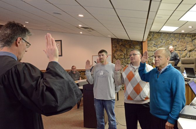 Craig Municipal Court Judge Kevin Peck, foreground, administers the oath of office to Craig City Council members, from left, Jarrod Ogden, Tony Bohrer and Gene Bilodeau. Bilodeau also was nominated to serve as assistant mayor.