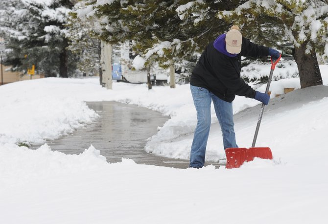 Steamboat Springs resident Robin Cross clears sidewalks in front of a business near Mount Werner Road on Monday morning.