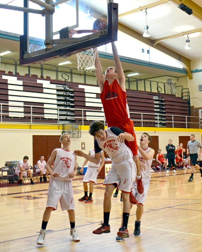 High Altitude Basketball player Garrett Bye gets a putback dunk at a tournament in Laramie, Wyo. The varsity team went undefeated and won the tournament.