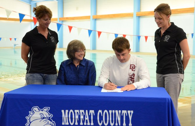 Moffat County senior Matt Hulstine signs a letter of intent Wednesday to swim at the University of Denver at the MCHS pool. With Hulstine were coach Anita Reynolds, from left, Hulstine's mother, Bonnie Hulstine, and coach Meghan Francone.