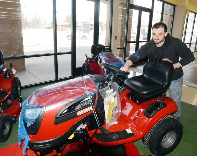 Sears delivery manager Jordan Worden pushes a lawn mower into place in front of a window at Sears' new Central Park Plaza location. The store, which still is open in its current location, is moving and hopes to be open at its new location in mid-May.