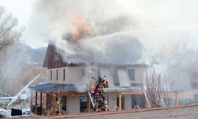 Firefighters from Oak Creek and Yampa battle a blaze Monday morning at 134 W. Williams St. in Oak Creek. The fire apparently began in the chimney and them spread underneath the roof of the home.