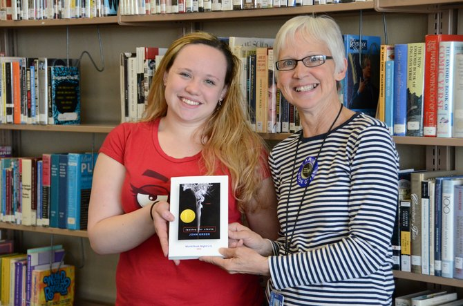 "Moffat County High School senior Jessi Scott, left, holds up ""Looking for Alaska,"" an award-winning novel by John Green. Robin Weible, right, of MCHS, gave Scott the book as part of World Book Night, a nationwide program distributing books to youths. MCHS gave out 240 free books Tuesday."