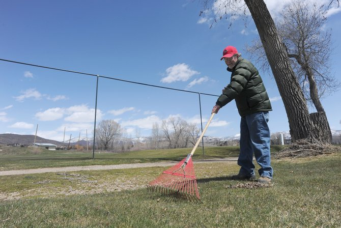 Volunteer Blase Arigo rakes leaves and dead grass Wednesday afternoon at the Steamboat Golf Club west of Steamboat Springs. Superintendent Jason Rivera is hopeful that the course will open Saturday.