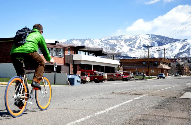 A cyclist cruises down Yampa Street on Wednesday. Although a proposal to add parks and a promenade to the downtown street did not earn the endorsement of the city's lodging tax committee, stakeholders on Yampa and downtown are pressing on with revitalization efforts.