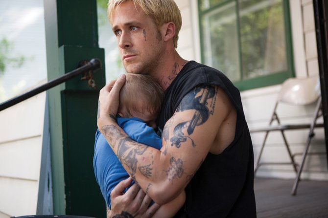 "Luke Glanton (Ryan Gosling) holds his infant son tight in ""The Place Beyond the Pines."" The movie is about a motorcycle stunt rider who turns to robbing banks to provide for his child."