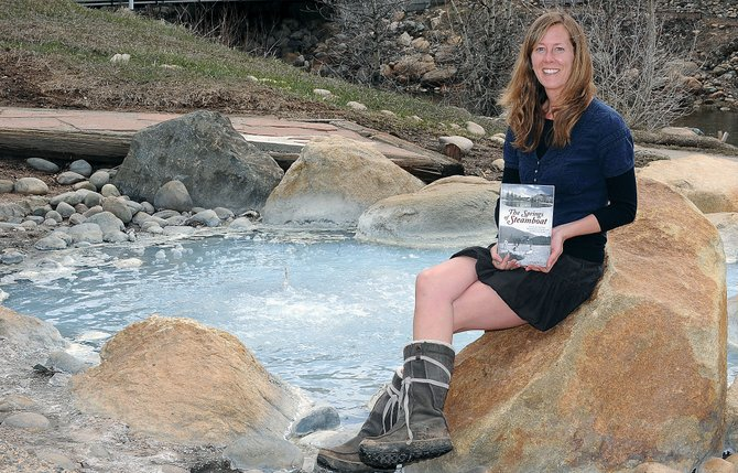"Local author Dagny McKinley holds her book ""The Springs of Steamboat"" in front of the Sulfur Spring in West Lincoln Park in Steamboat Springs. McKinley will have a signing for the book May 11 at the Tread of Pioneers Museum."