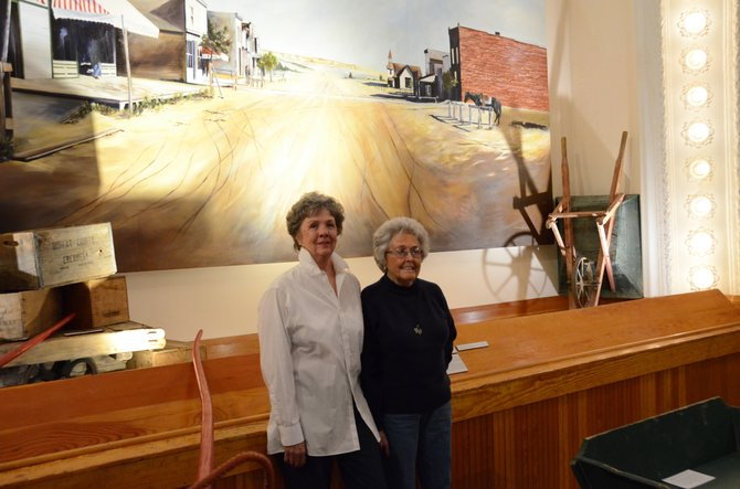 Delaine Voloshin (left) and Barbara Baker stand in front of a mural of Craig in 1896 in the Museum of Northwest Colorado. Both women have volunteered their time as members of the board for over 25 years, and were there when the museum moved from the courthouse to its current location.