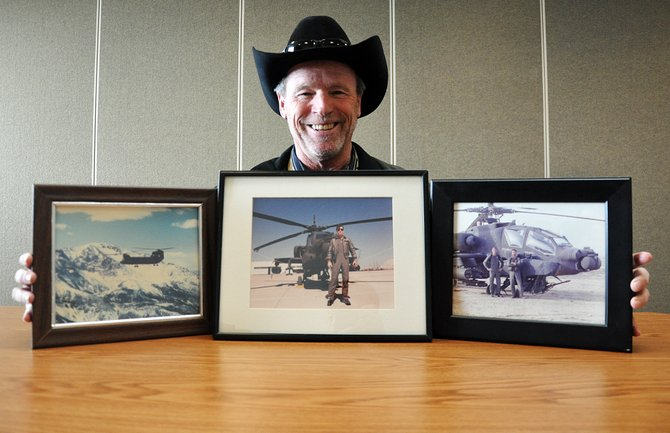 Dean Smith, assistant manager at Yampa Valley Regional Airport, poses with photos that chronicle his extensive career as a military pilot. Smith has clocked 26,000 hours in the cockpit and flew Apache helicopters on combat missions in Afghanistan in 2001.