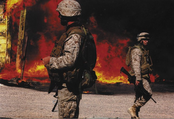 Marines walk past the aftermath of a mortar explosion in Fallujah, Iraq, during one of Ty Upson's two deployments to the country.