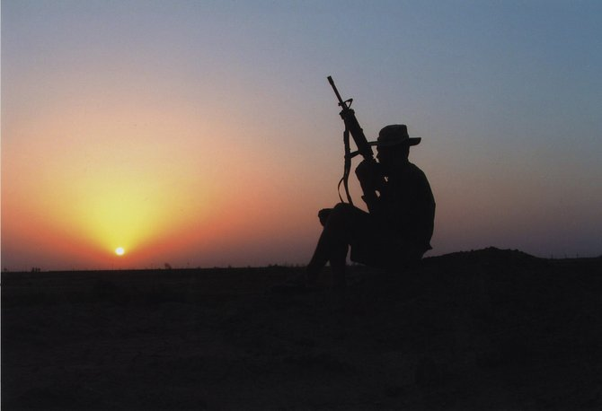 "Hahn's Peak resident and U.S. Marine Ty Upson takes in a summer sunset near Fallujah, Iraq, in 2006. According to the staff bio for the Steamboat Springs Winter Sports Club coach, ""spending two years in Mesopotamia taking on bad guys did little to tone down his zest and enthusiasm for skiing."""