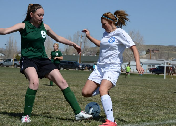 Alex Samuelson fights for the ball with a Rangely defender Saturday at Woodbury Sports Complex in Craig. Moffat County girls soccer won, 7-0, and improved to 7-5 this season.