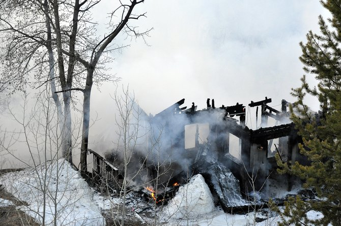 Smoke billows from the charred remains of a home on Elk Lane in Steamboat Springs on Saturday morning.