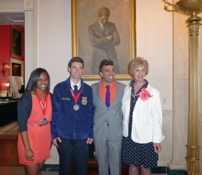 Mike Espy, second from the left, a sophomore at Little Snake River Valley School in Baggs, Wyo., poses in front of the  John Kennedy Painting at the White House with, from left, Cece Poole, Bobak Ferdowsi, engineer on Mars Rover for Jet Propulsion Laboratory, and Carolyn Hicks, Little Snake River Valley School science teacher. Espy was invited to Washington D.C. to participate in the White House Science Fair after placing second in the DuPont Challenge.