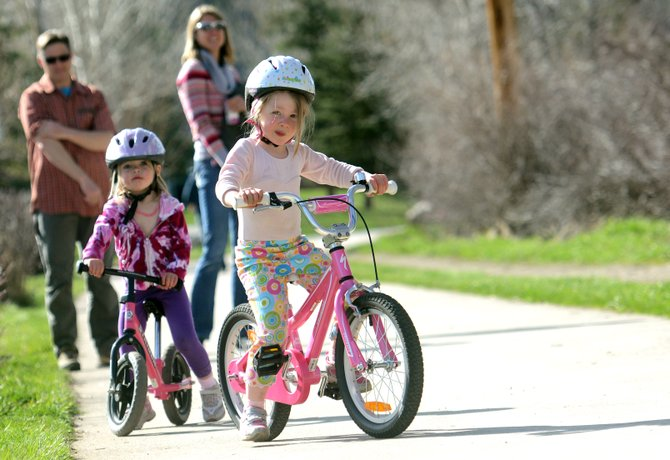 Inga Palmquist, 4, and Erika Palmquist, 3, survey the Yampa River Core Trail in Steamboat Springs on a sunny Friday afternoon in May as they work on their bicycling skills. Summer sports are descending on Steamboat quickly, and competition series such as the Steamboat Springs Running Series and Town Challenge Mountain Bike Race Series aren't far off. Dirt trails still are too muddy and snowy for use, however.