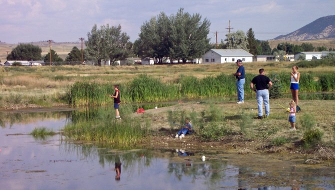 Craig law enforcement officers and local children participate in Cops and Kids Fishing Day in 2003 at Little Rascals Pond. This year's event, which is open to children 12 years of age and younger, takes place from 5 to 7 p.m. on Wednesday, May 29.