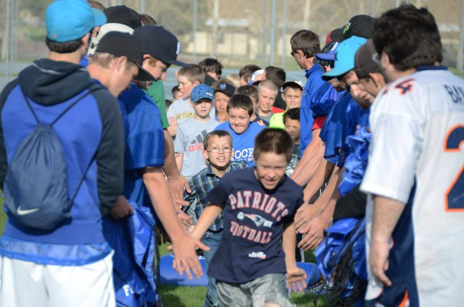 Players at the Big Blue Football Camp run through a tunnel of Moffat County High School coaches and players at the camp's conclusion Thursday evening. The camp showed youths from kindergarten through fifth grade the fundamentals of football.