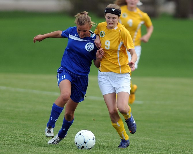 Moffat County's Jazmine Swindler (left) races to the ball against Emma Lichina of Manitou Springs. The 23rd-seeded Bulldogs came up just short in their playoff game against No. 10 Manitou on Friday at Jackson Field in Greeley. They lost, 2-1, in double overtime.