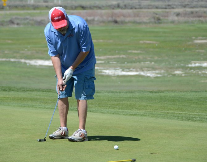 Tony Aragon watches his ball track for the hole on the 18th green Saturday at Yampa Valley Golf Course. Aragon was playing with teammates Ken Harjes, Rick Holford and John Whinery in the Dirt Hog Scramble, the first tournament of the season at YVGC. They shot a 64 as a team.