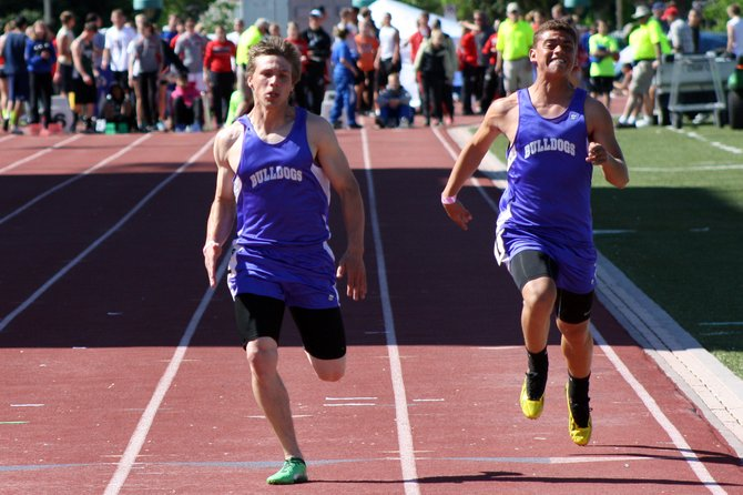 Kelly Campbell (left) and Alan Flores run in the 100-meter finals at the 3A Western Slope League Championship in Grand Junction Saturday. Both Bulldogs will be participating at the state meet for Moffat County next weekend.