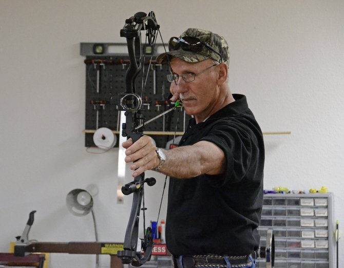 Allen Jenkins, owner of Sand Springs Archery in Craig, prepares to sling an arrow at his store on 80 E. Fourth St., Suite 105. In addition to adding the Hoyt brand Jenkins recently moved into a larger space equipped with a target to allow customers to test a variety of bows before purchase.