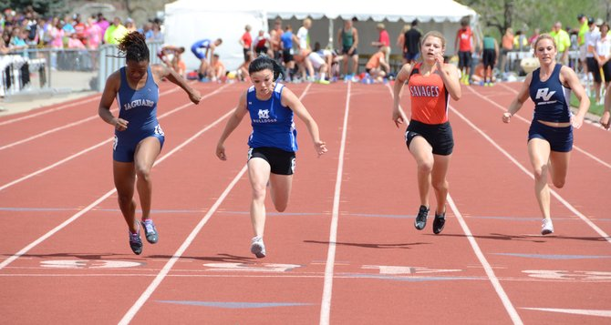 Kayla Pinnt leans for the finish line in the Class 3A girls 100-meter dash finals Saturday at Jeffco Stadium. Pinnt placed second in a photo finish to James Irwin's Alicia Lawrence (at Pinnt's left in dark blue). Pinnt ran a season-best time 12.39 seconds to Lawrence's 12.38.