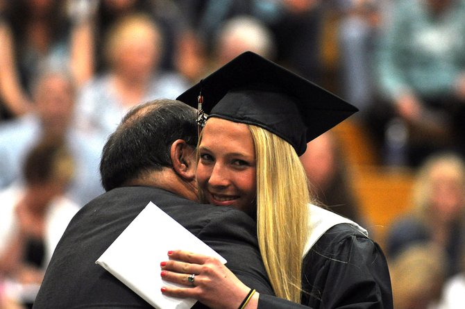 Savannah Williams hugs Brian Hoza on Sunday during the graduation ceremony at Hayden High School. The school graduated 31 seniors.