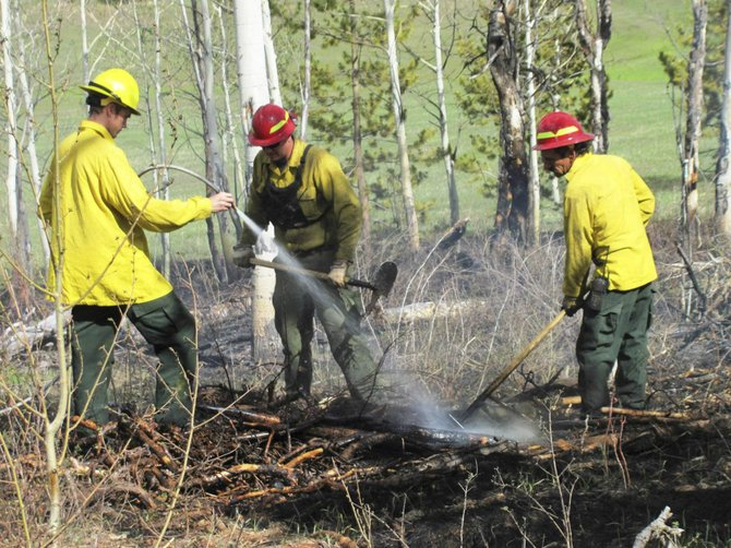 Firefighters work a wildfire Wednesday along Routt County Road 16 in South Routt County. Embers from a slash pile started the fire.