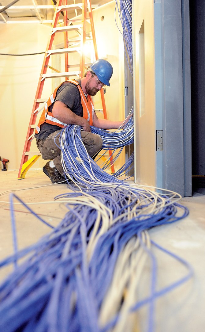 Sean Thornberry, of Northwest Data Systems, runs large amounts of wiring inside Casey's Pond Senior Living.