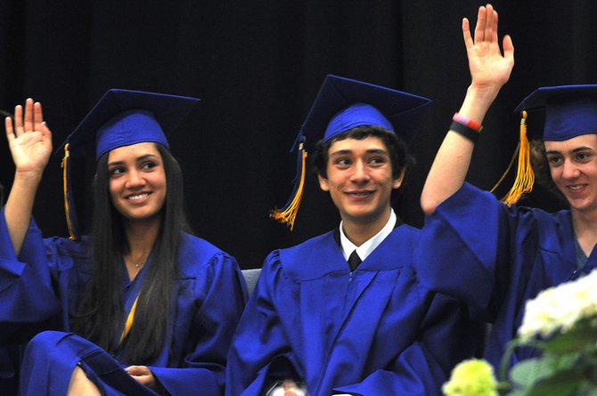 Heritage Christian School graduates, from left, Shealie Jenkins, Stephen Hathaway and Kieran Buccino raise their hands Sunday when asked by a speaker if they are ready for life after high school.