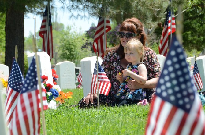 Jeanie Gra, of Fruita, sits with her granddaughter Alyssa Fears, 2, of Craig, at the Craig Cemetery on Memorial Day. Roughly a hundred people gathered at the cemetery to remember the men and women of the United States who lost their lives in battle.