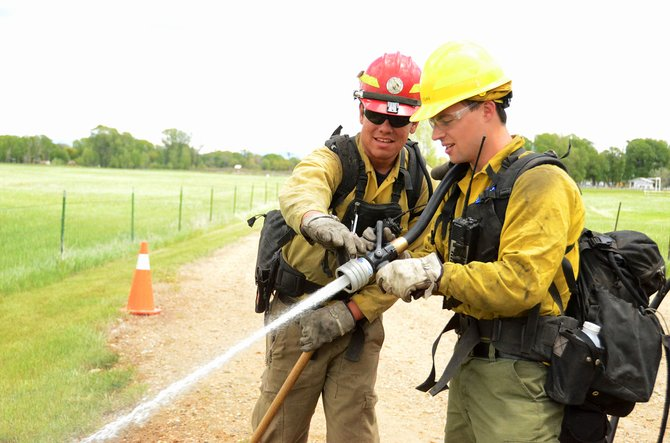 Assistant engine Capt. Ariel Fick, left, shows trainee Chris Young how to operate the nozzle on a fire hose as a group of Northwest Colorado firefighters gathers at Loudy-Simpson Park in Craig in May to prepare for the wildfire season. The goal was to mimic various situations they might find themselves in while fighting wildfires. The firefighters are from Craig, Meeker, the Bureau of Land Management, Dinosaur National Monument and Browns Park National Wildlife Refuge.