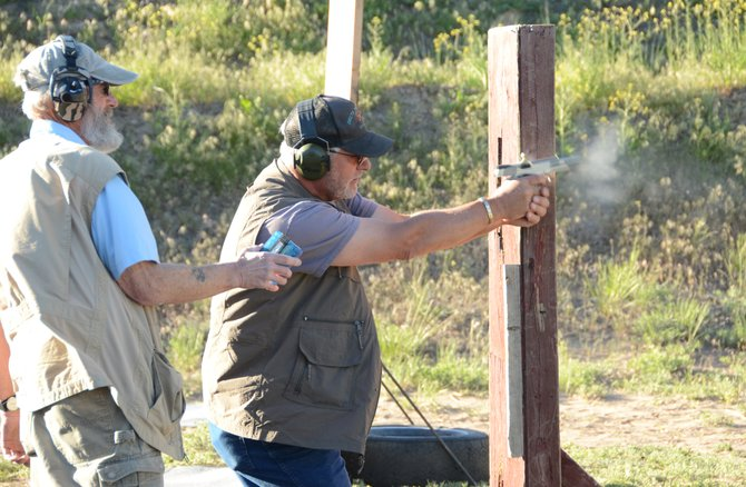 Mike Beldon shoots his way through a scenario Friday at the Cedar Mountain Range Sportsman Club. Beldon and a group of nine others from Moffat County were shooting defensive pistol, one of a variety of of shooting sports done in Craig during the spring and summer.