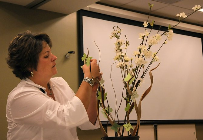 The Memorial Hospital Chief of Organizational Excellence attaches paper butterflies with the names of cancer survivors to ornamental branches during the hospital's National Cancer Survivors Day tea party Sunday, June 2. The secular holiday honors the almost 14 million cancer survivors in the US, as well as those still battling the disease.