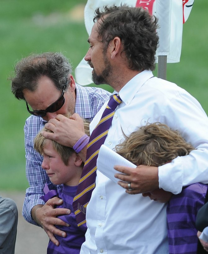 "Mike Kirlan hugs Oliver Cardillo during Monday afternoon's memorial service for Kirlan's son, Asher Lesyshen-Kirlan, at the base of the Howelsen Hill jump complex. The boys came on stage to sing the ""Star Spangled Banner"" as part of a tribute to the 9-year-old boy, who died last week. Oliver's father, John Cardillo, middle, and his brother, Henry, also were on stage for the tribute."