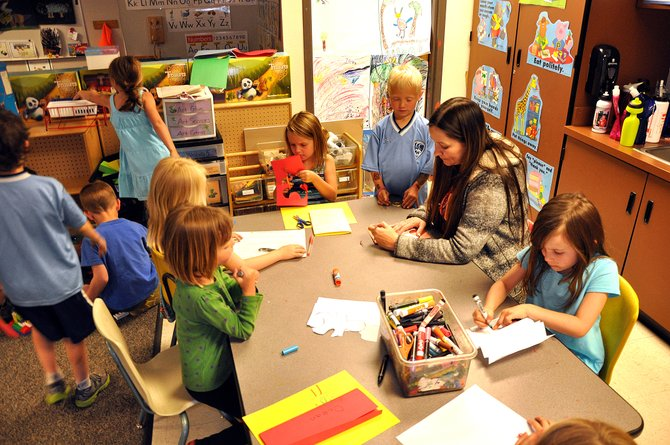 Strawberry Park Elementary School teacher Carol Harris helps her kindergarten students with art projects Thursday. Of the 24 new out-of-district applications for Steamboat Springs School District, 12 are for new kindergarten students.