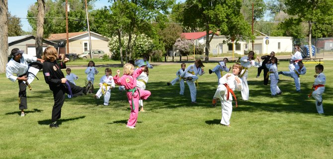 Paul Cruz, far left, leads his Kom Do Kwan students through kicking drills Friday morning at City Park.