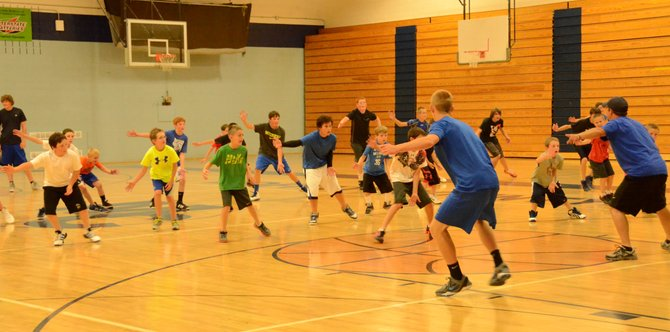 The boys at Moffat County's youth basketball mini-camp slide through a defensive drill led by MCHS head coach Eric Hamilton and some players from the team in the MCHS gym.