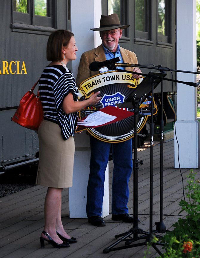 Standing in front of the historic Marcia passenger car, Mayor Terry Carwile accepts Craig's official induction into the Train Town USA Registry from Director of Public Affairs for Union Pacific Sarah Cassidy on Tuesday evening. The registry commemorates towns that have played an important role in railroad history.