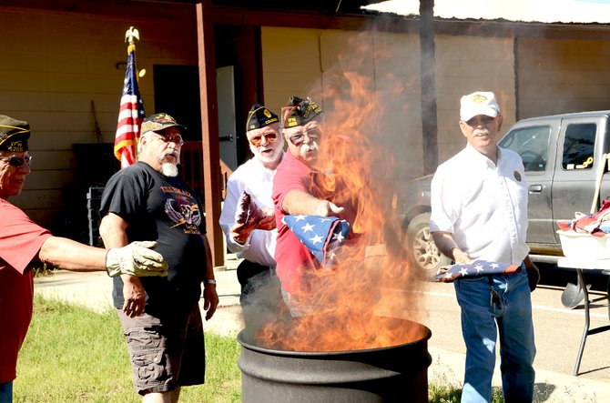 Mark Wick, the commander elect for the Craig's VFW Post 4265, and fellow veterans burn retired flags Friday, which was nationally recognized as Flag Day. The group ignited roughly 800 retired flags given to them by the community.