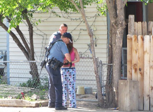 Officers take a suspect into custody outside of a home at 796 Barclay St., where police executed a search warrant and made two arrests Tuesday morning. Another search warrant was executed at 974 Aiken St.