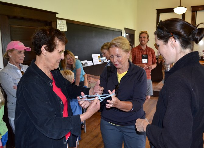 Ann DeYoung, of Burlington, Vt., left, and B.J. Hess, of Boston, play a game of cat's cradle Tuesday at the one-room Mesa Schoolhouse while Annmarie Kirkpatrick, of Fort Collins, watches. Kirkpatrick is one of the leaders of a travel tour group comprising grandparents and their grandchildren who are visiting Steamboat this week.