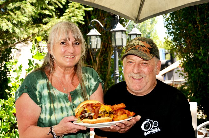 Husband and wife O.P. Bar & Grill team Diana and Delbert Kenz hold their monstrous Triple Cheeseburger that costs $14.50. The Craig restaurant won best hamburger in the 2013 Best of Moffat County survey.