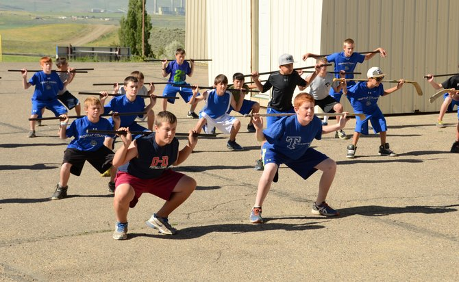 Incoming seventh- through ninth-graders work through strength and conditioning exercises outside the Moffat County High School weight room. About 60 Bulldogs have been attending the training days all summer to get ready for the coming sports year.