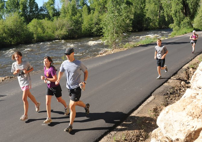 Rachael Green, center, and Rodney Green, right, run with Lark Skov in 2011 during the Steamboat Springs Running Series' Mountain Madness event. This year's race will start at 7:30 a.m. Saturday and will serve as a benefit to longtime race director Scott Blair.