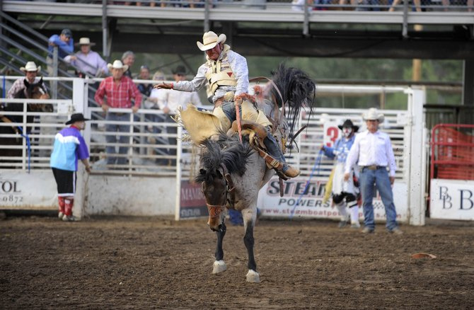 Wade Mosher, of Hugo, competes in the saddle bronc riding event during the Fourth of July rodeo.