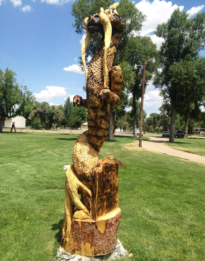"""Upon a Time,"" depicting a dragon coming out of a book, by Chad Stratton, is now situated at the north end of City Park in Craig. Every carving but one from the 2013 Whittle the Wood Rendezvous has its space picked out around the city."