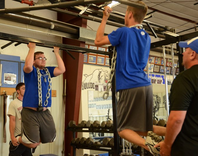 Keith Smith, left, works through his set of pullups Tuesday evening at the Moffat County High School weight room. Smith and other returning sophomores, juniors and seniors have been in the weight room all summer, getting prepared for the upcoming high school football season.